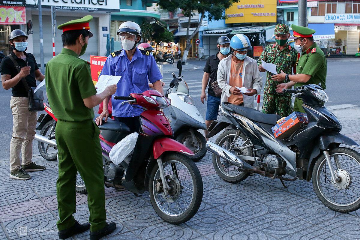 Lực lượng chức năng kiểm tra giấy đi đường ngày đầu Đà Nẵng cách ly xã hội cao hơn chỉ thị 16, tối 31/7. Ảnh: Nguyễn Đông.