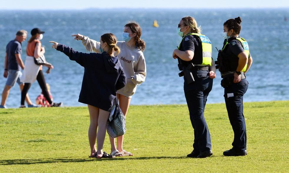 Cảnh sát nói chuyện với người dân trên bãi biển ở thành phố Melbourne, Australia, hôm 2/9. Ảnh: AFP.