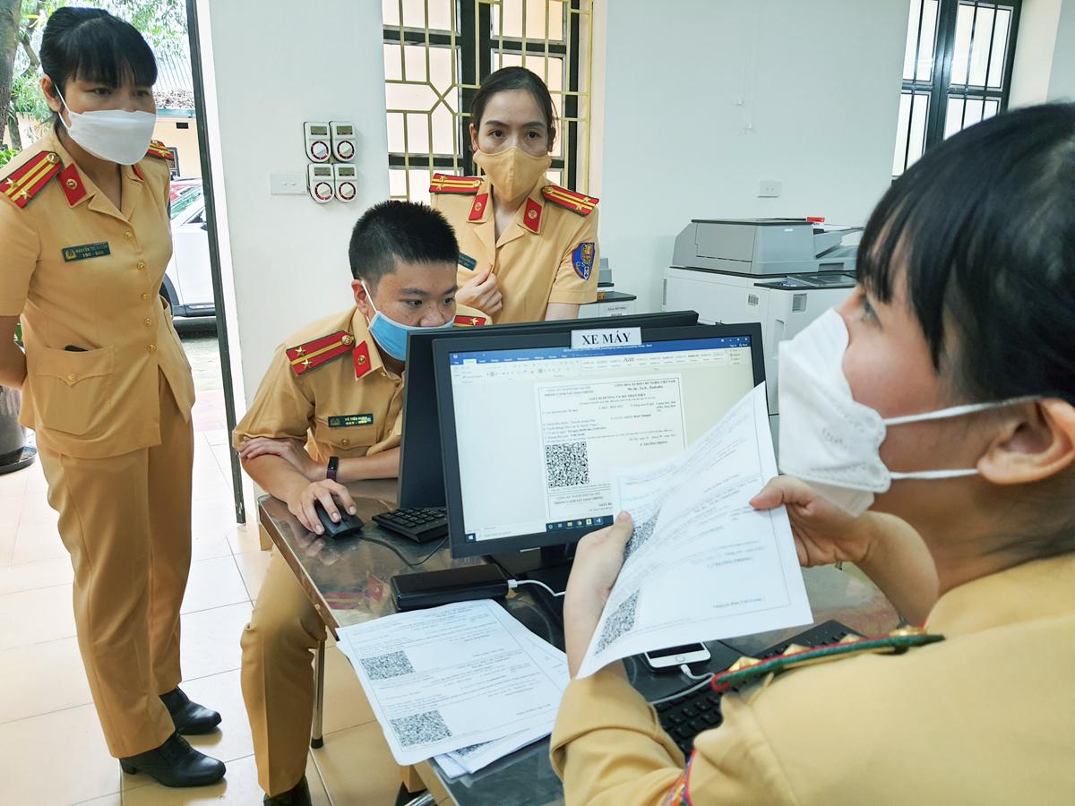 Cán bộ, chiến sỹ PC08 trao đổi nghiệm vụ cấp giấy đi đường theo mẫu mới, chiều 5/9. Ảnh: Võ Hải.