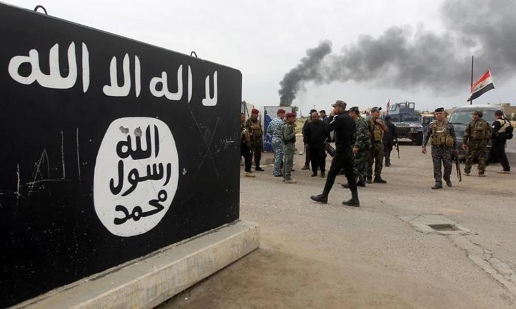 Lực lượng an ninh Iraq và các chiến binh người Shiite tập hợp bên cạnh một bức tường vẽ cờ của IS ở thành phố Tikrit hồi tháng 4/2015. Ảnh: AFP.