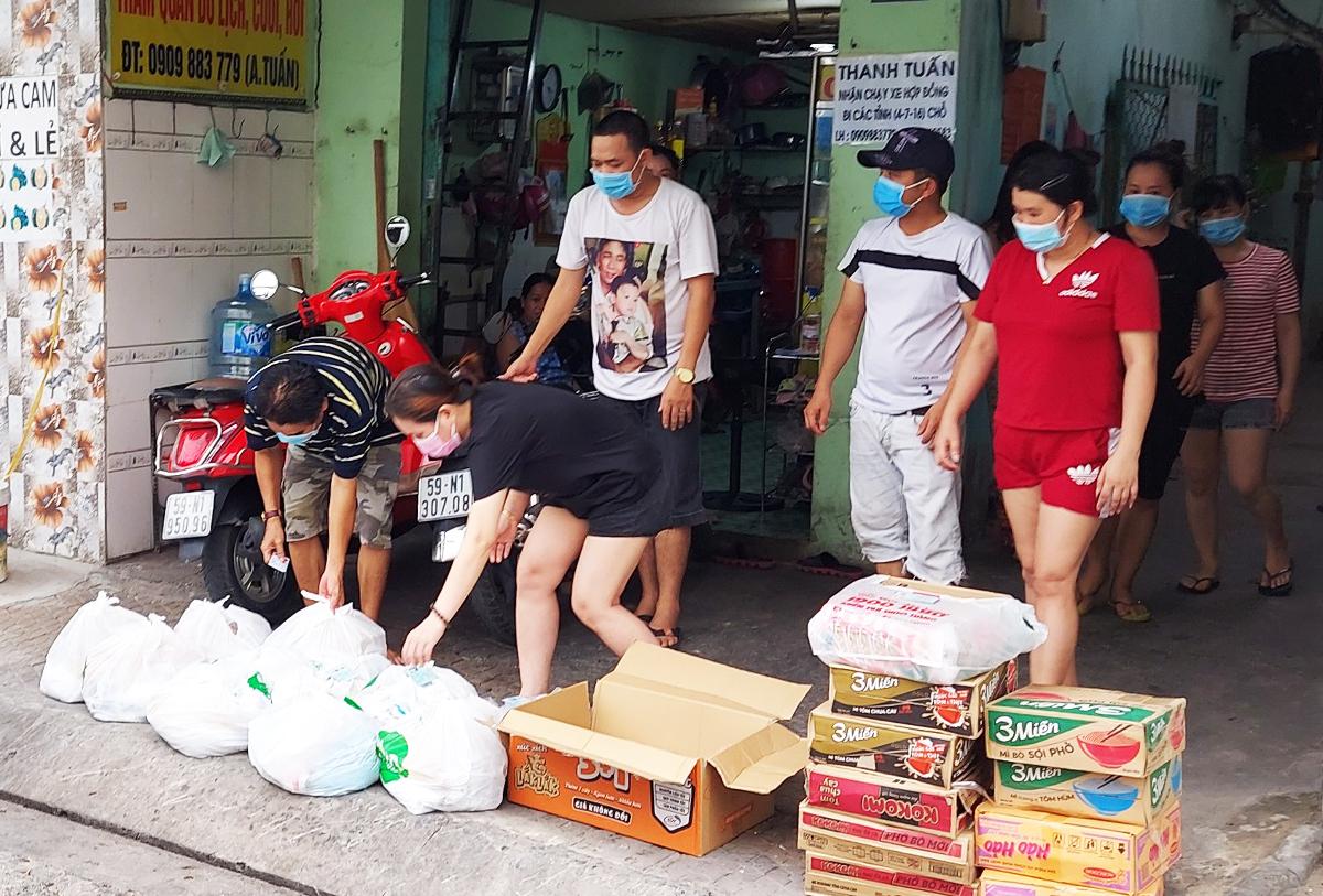 Người dân ở xóm trọ nhận lương thực từ đội SOS Trung tâm an sinh. Ảnh: Hồng Duyên