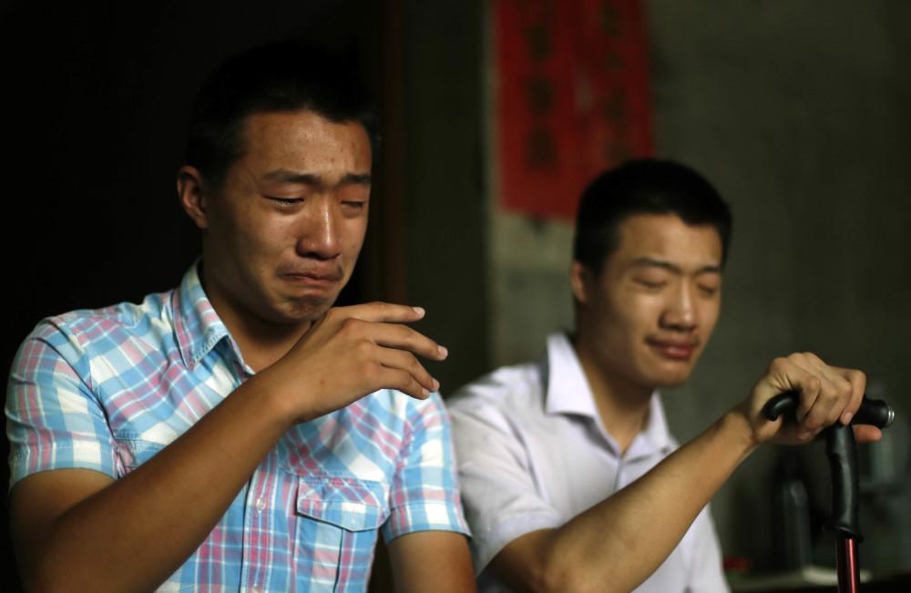 Hai anh em Hoa Đông (trái) và Hoa Lương (phải), khóc khi kể về sự hy sinh của mẹ tại nhà riêng hôm 30/8. Ảnh: QQ