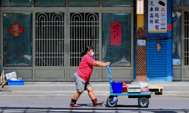 Một phụ nữ đeo khẩu trang, đẩy xe chở đồ tại thôn Phòng Cảng, huyện Bình Đông, Đài Loan, trong tháng 8. Ảnh: Guardian