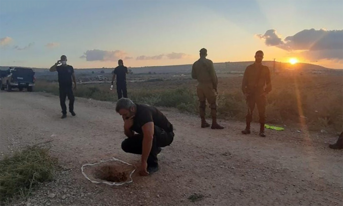 Điều tra viên Israel kiểm tra miệng hầm trên đường sau vụ 6 tù nhân Palestine vượt ngục ngày 6/9. Ảnh: IPS.