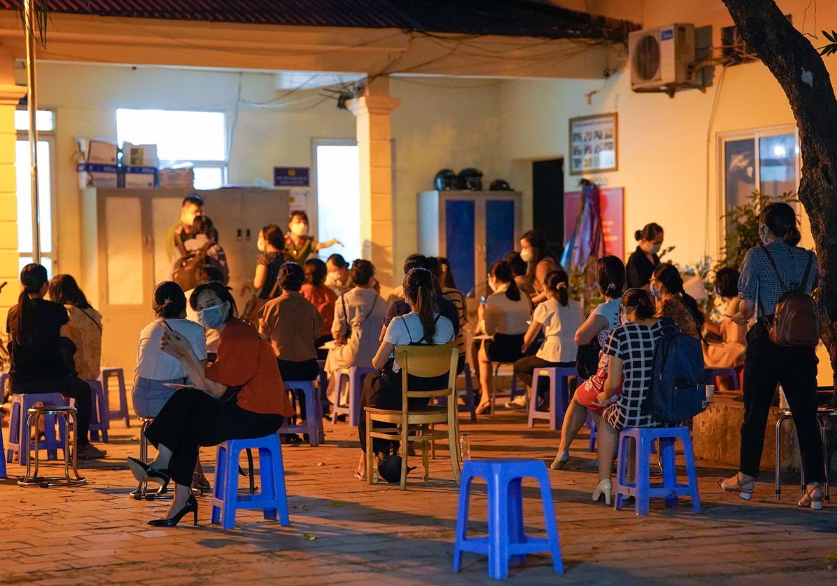 Tối 6/9, nhiều người ngồi đợi tại trụ sở Công an phường Mễ Trì để làm thủ tục cấp giấy đi đường theo mẫu mới. Ảnh: Phạm Chiểu.