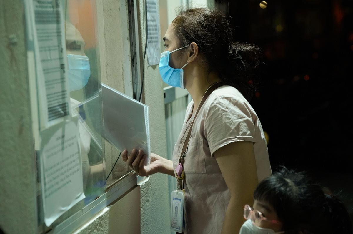 Chị Phạm Thị Yến (dược sĩ tại một phòng khám Hàn Quốc tại phường Mễ Trì, quận Nam Từ Liêm) đến xin giấy đi đường cho nhân viên phòng khám. Ảnh: Phạm Chiểu.