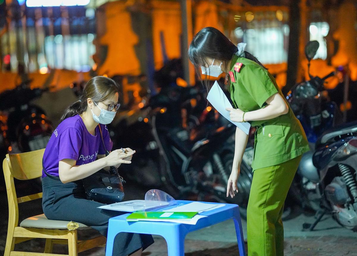 Nữ công an phường Mễ Trì hướng dẫn người đến làm thủ tục cấp giấy đi đường. Ảnh: Phạm Chiểu.