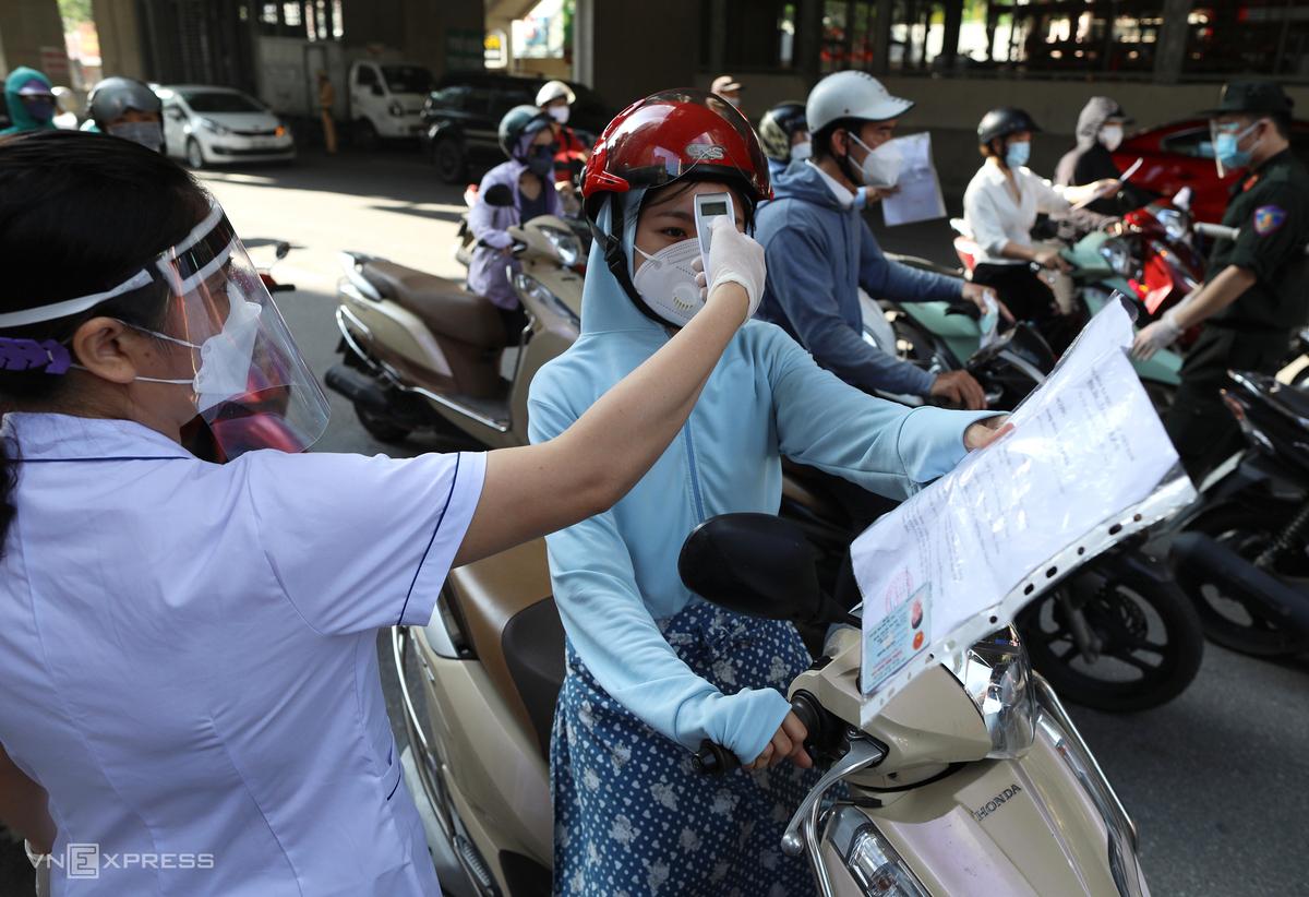 Lực lượng chức năng đo thân nhiệt trước khi kiểm tra giấy đi đường người dân, sáng 6/9. Ảnh: Ngọc Thành