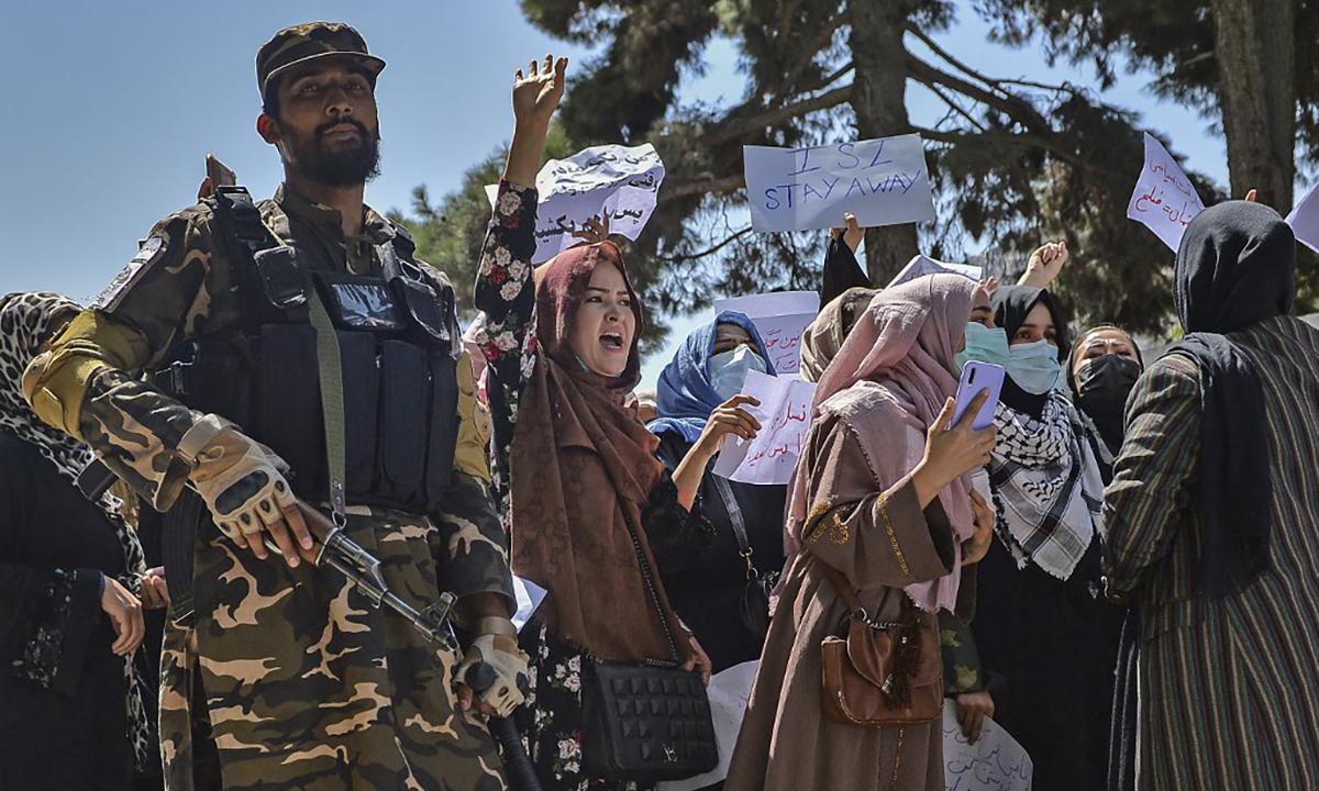 Một tay súng Taliban đứng cạnh nhóm phụ nữ biểu tình trước đại sứ quán Pakistan ở Afghanistan ngày 7/9. Ảnh: AFP.