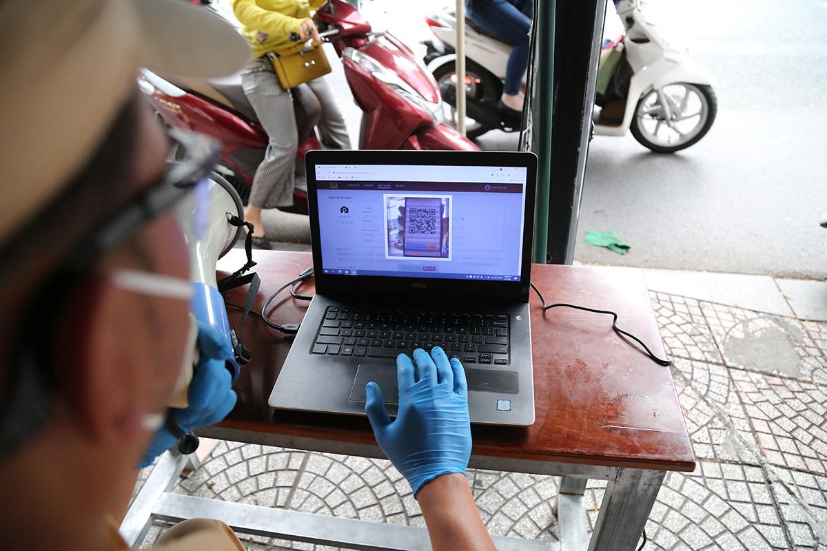 Cảnh sát kiểm tra mã QR code của người đi đường quét thông qua máy tính kết nối với camera tại chốt kiểm soát đường Lê Văn Duyệt, chiều 7/9. Ảnh: Đình Văn