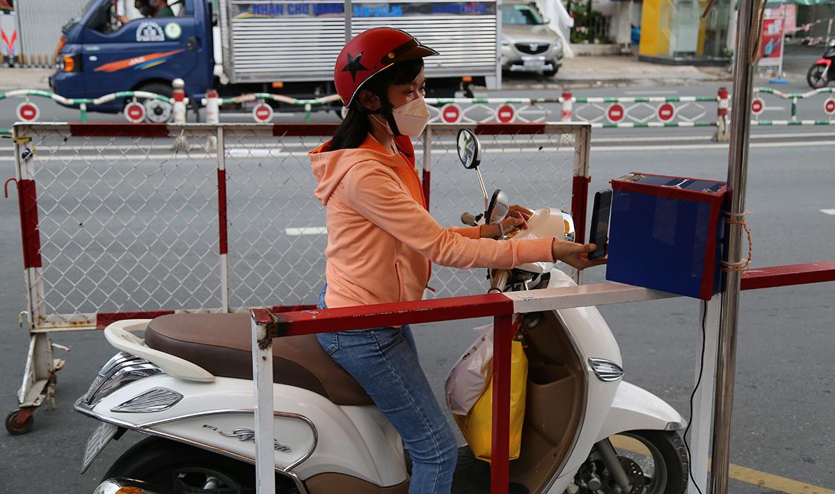 Người đi đường đưa điện thoại trước mắt camera để quét mã di biến động ở chốt đường Phan Đăng Lưu, quận Phú Nhuận. Ảnh: Đình Văn