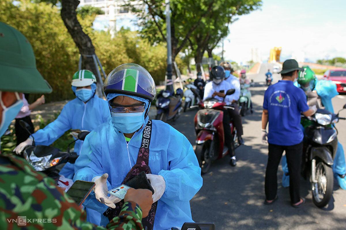 Lực lượng tại chốt cầu Rồng kiểm tra thủ công đồng thời mã QRCode và giấy tờ tuỳ thân của người ra đường, sáng 5/9. Ảnh: Nguyễn Đông.