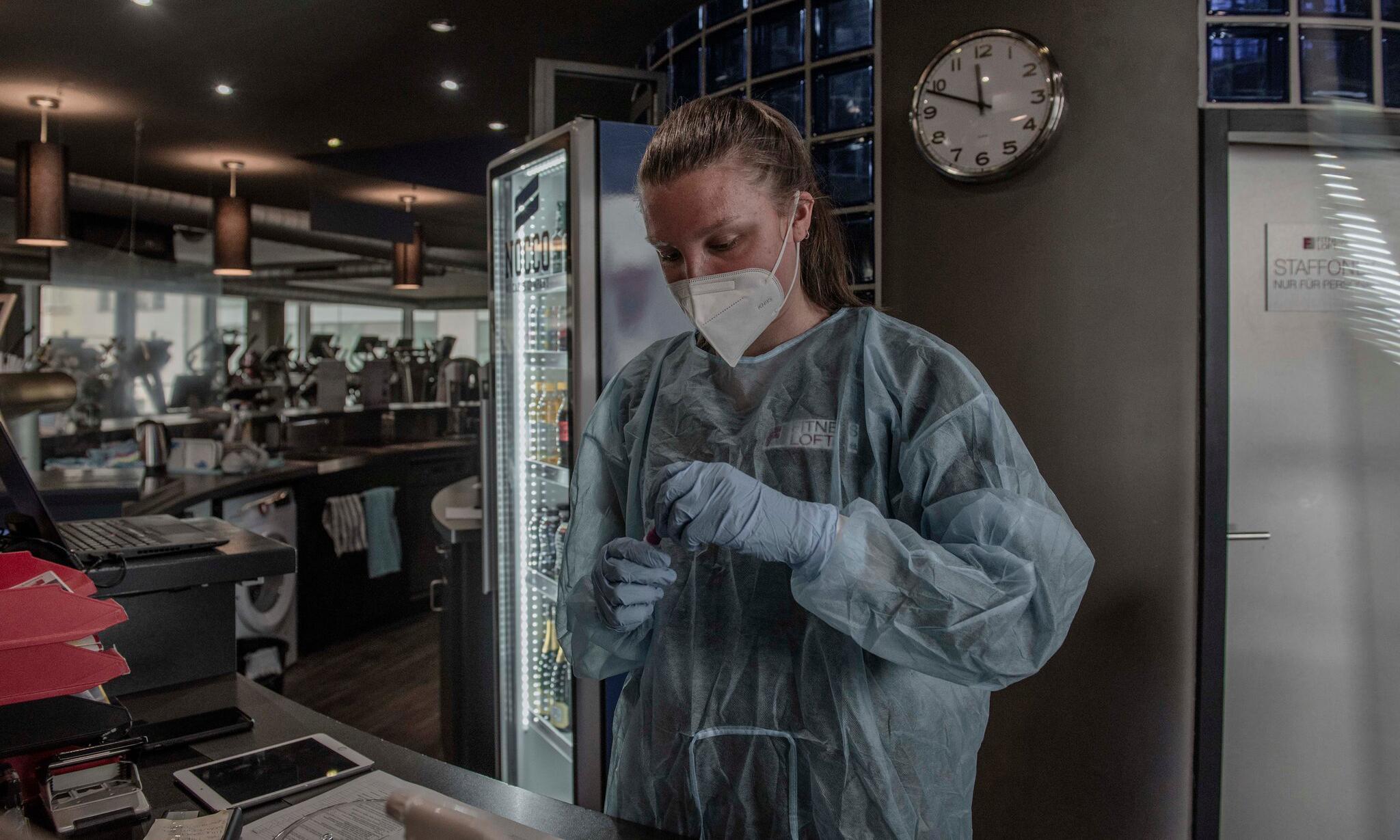 Nhân viên y tế tại điểm xét nghiệm nhanh được thiết lập trong một phòng gym ở thành phố Saarbrucken, bang Saarland, Đức, hồi tháng 6. Ảnh: NY Times.