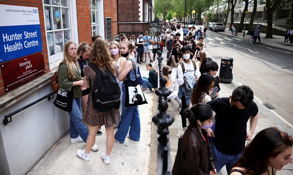 Thanh thiếu niên chờ đợi bên ngoài một điểm tiêm chủng vaccine Covid-19 ở London hôm 5/8. Ảnh: Reuters.