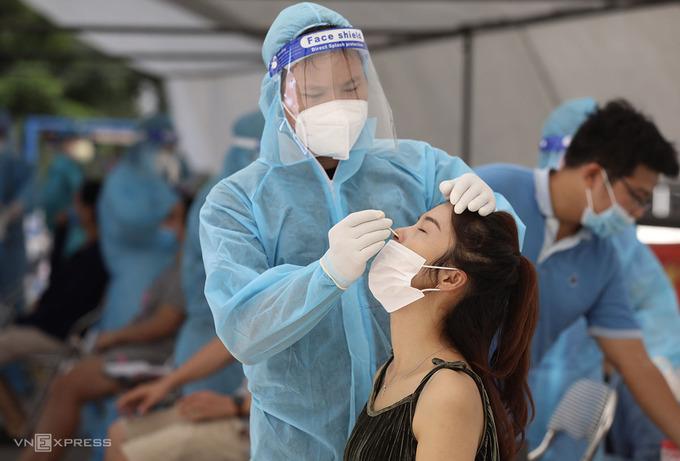 Nhân viên y tế lấy mẫu xét nghiệm cho người dân ở khu đô thị Linh Đàm, quận Hoàng Mai sáng 18/8. Ảnh: Ngọc Thành
