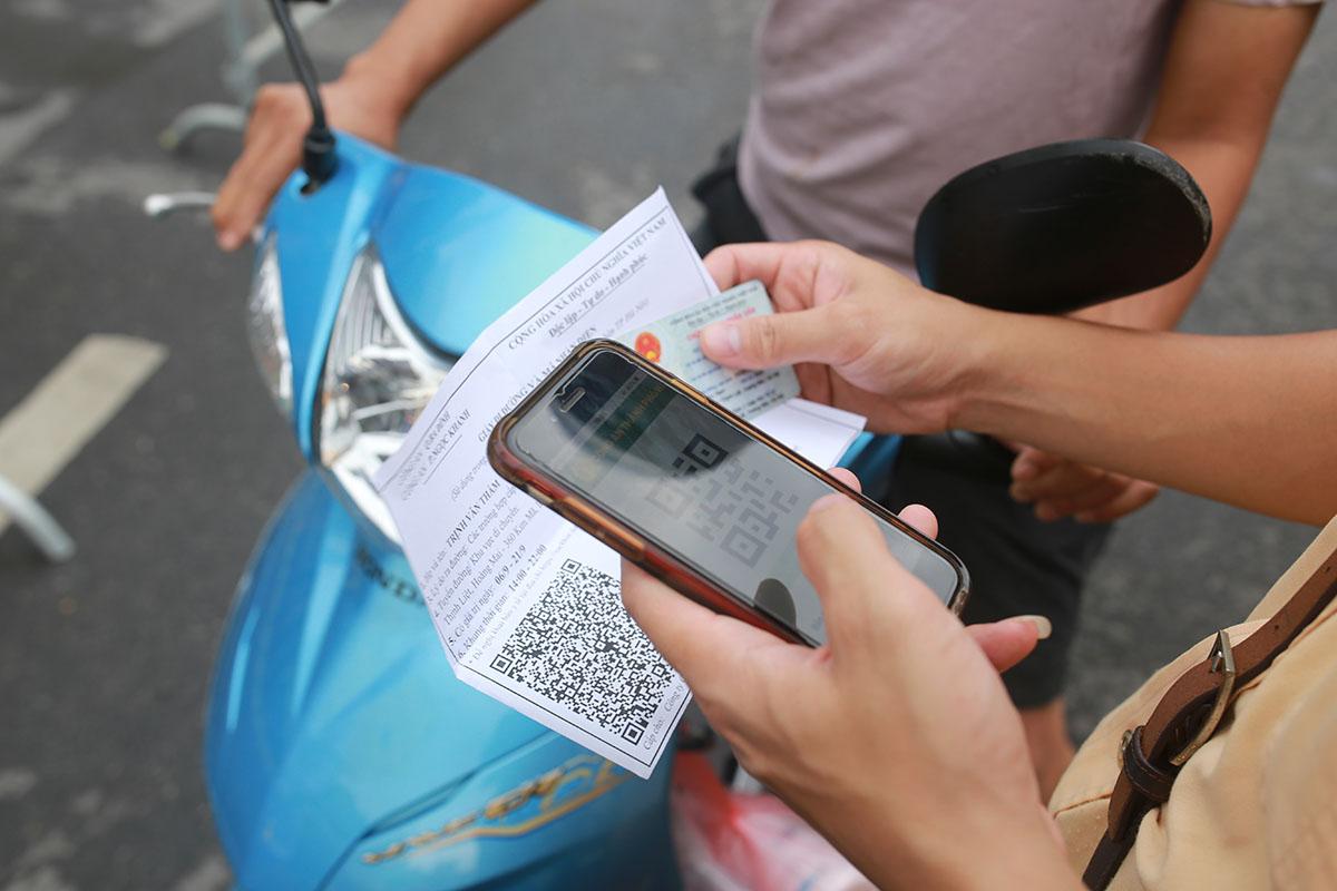 Cảnh sát giao thông quét mã QR-Code mẫu giấy đi đường mới. Ảnh: Tất Định.