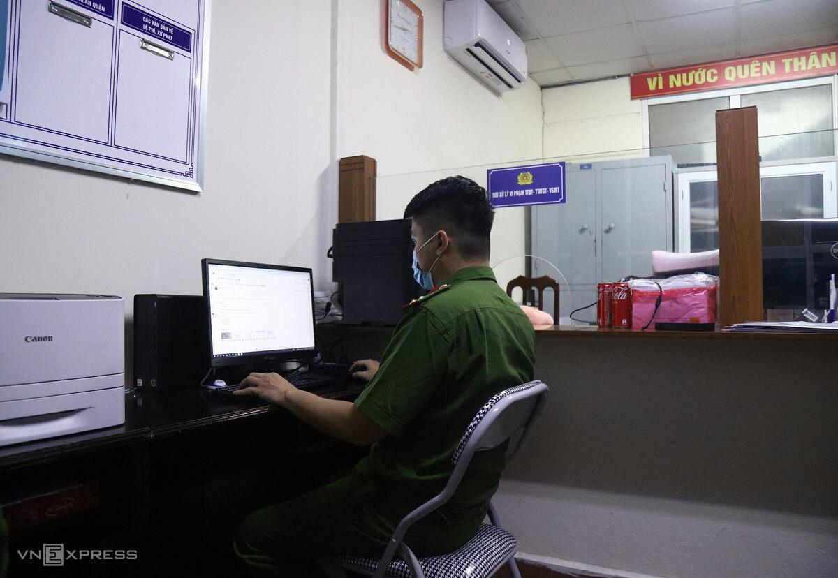 Cán bộ công an phường Dịch Vọng Hậu, quận Cầu Giấy ngồi rà soát thông tin hồ sơ doanh nghiệp gửi về, đêm 6/9. Ảnh: Phạm Dự