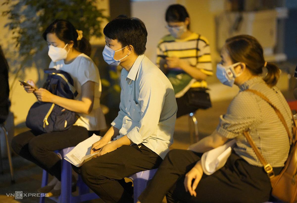 Nhân viên hành chính nhân sự các công ty ngồi chờ nộp hồ sơ cấp giấy đi đường tại trụ sở Công an phường Mễ Trì, quận Nam Từ Liêm, tối 6/9. Ảnh: Phạm Chiểu