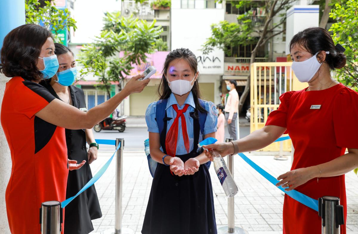 Học sinh trường Tiểu học Đinh Tiên Hoàng, quận 1 được rửa tay sát khuẩn, đo thân nhiệt trước khi vào lớp hồi tháng 5/2020. Ảnh: Quỳnh Trần