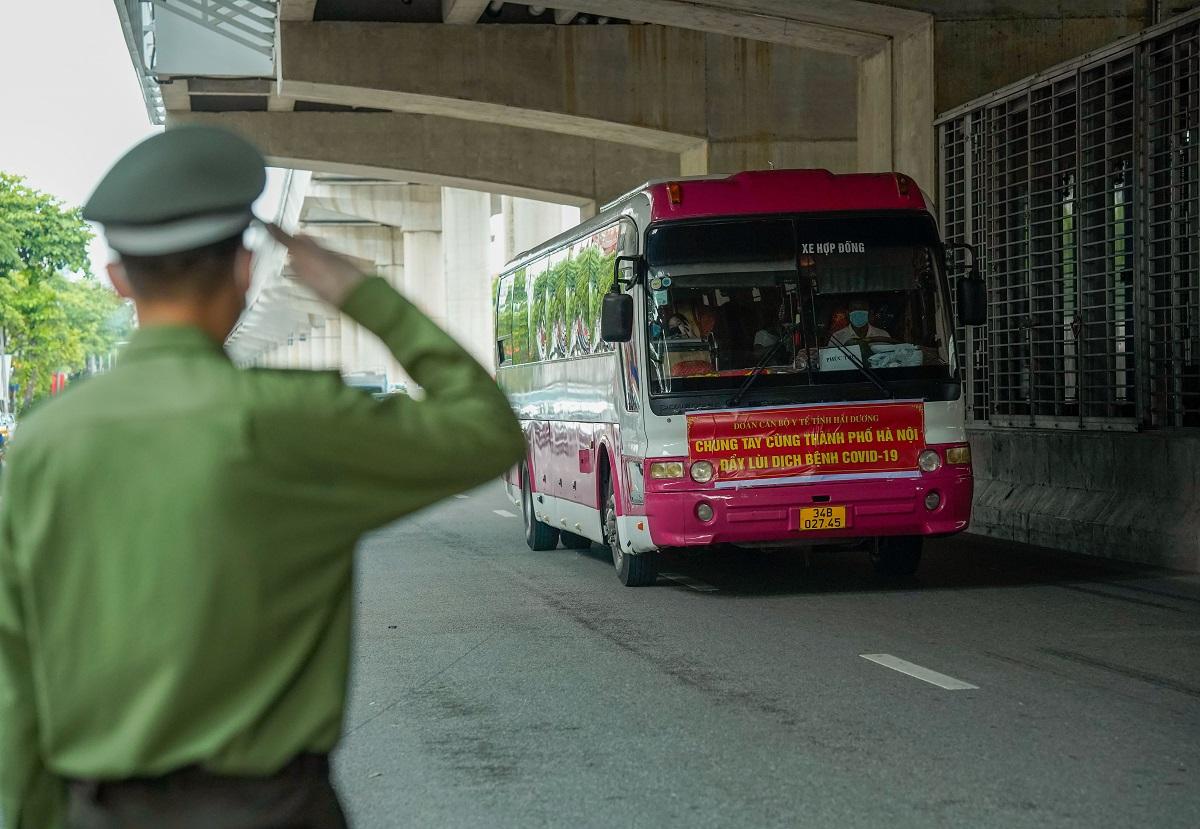 Gần 4.000 nhân viên y tế của 11 tỉnh, thành đã đến Hà Nội hỗ trợ việc xét nghiệm và tiêm vaccine. Trong ảnh, cán bộ công an tại chốt kiểm soát cầu Diễn giơ tay chào khi đoàn cán bộ y tế Hải Dương đi qua chốt chiều 9/9. Ảnh: Phạm Chiểu.
