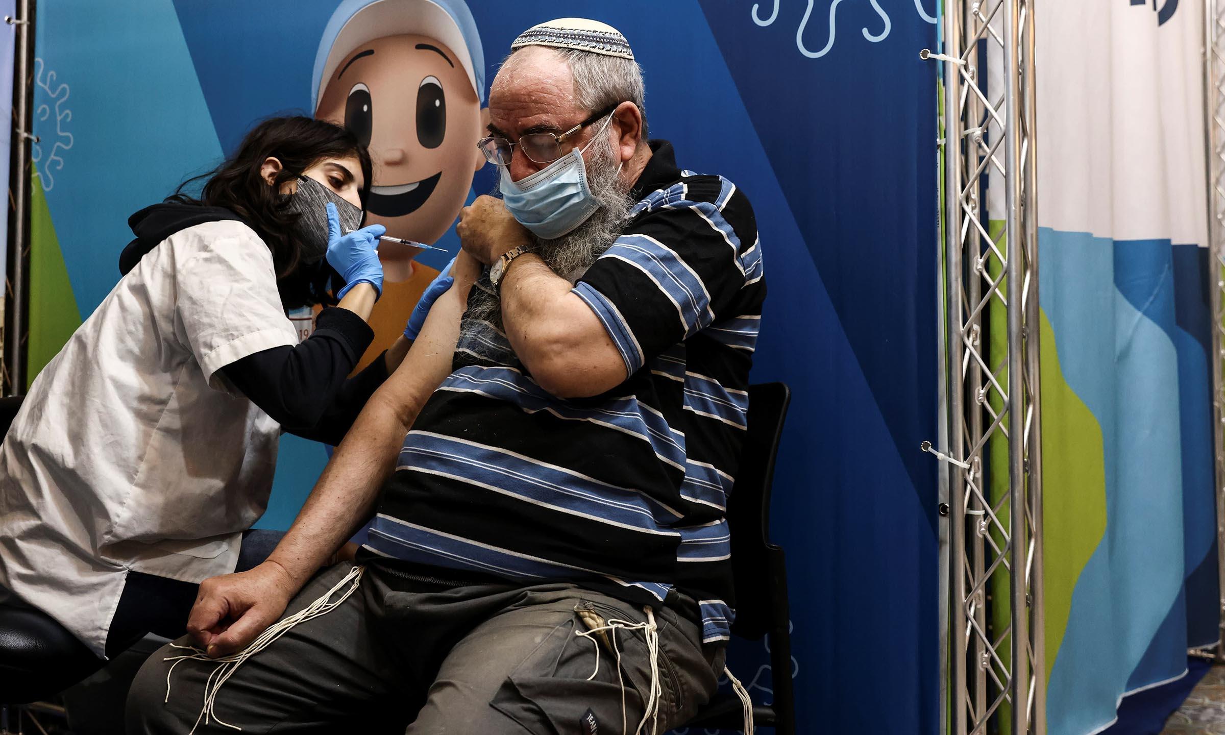 Một người đàn ông được tiêm liều vaccine Covid-19 thứ ba tại Jerusalem hồi giữa tháng 8. Ảnh: Reuters.
