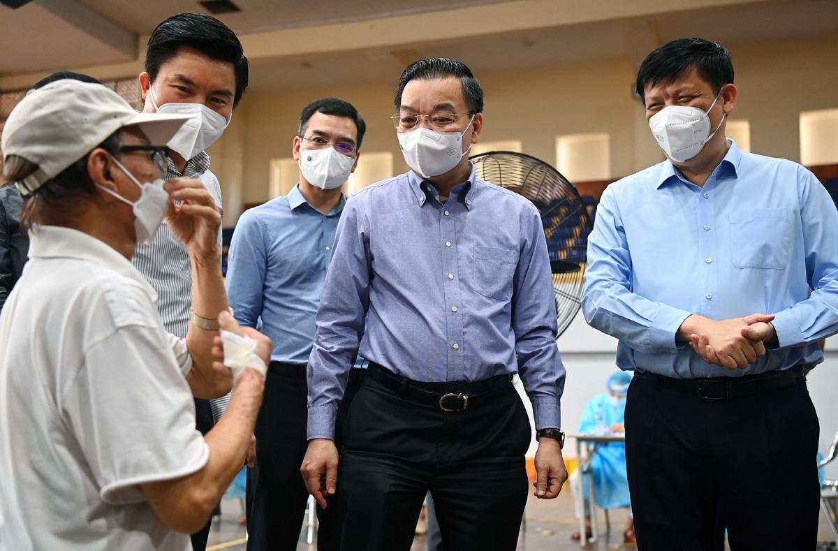 Từ phải qua, Bộ trưởng Y tế Nguyễn Thanh Long, Chủ tịch Hà Nội Chu Ngọc Anh kiểm tra điểm xét nghiệm, tiêm vaccine tại nhà thi đấu Trịnh Hoài Đức, quận Đống Đa, sáng 10/9. Ảnh: Giang Huy.
