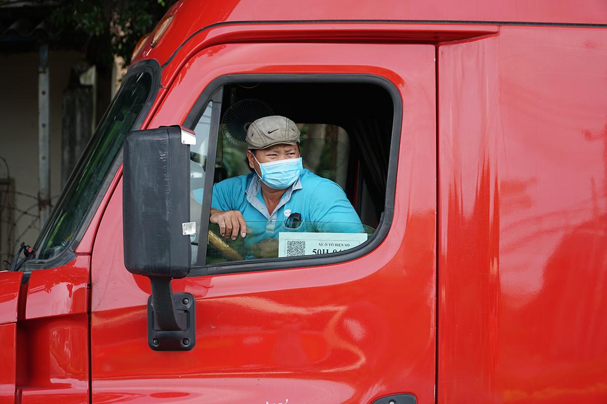 Ông Lê Hữu Thế ngồi chờ được giải quyết để lái xe container vào thành phố giao hàng. Ảnh: Trường Hà