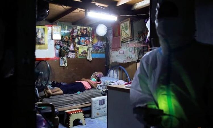 Một bệnh nhân Covid-19 nằm trên giường khi các tình nguyện viên đến hỗ trợ bà ngày 3/8. Ảnh: Reuters.