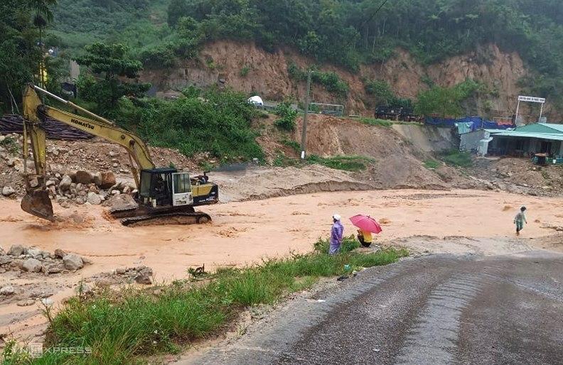 Máy múc đang gạt đất đá, tạo dòng chảy tránh nước tràn vào nhà dân ở suối Đắk Ba Sao chảy qua đường ĐH1, trưa 11/9. Ảnh: Đắc Thành.