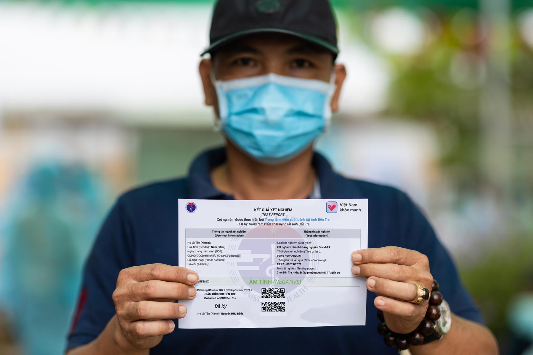 Một người dân hoàn thành xét nghiệm và nhận được kết quả xét nghiệm có QR code. Ảnh: Tài Nguyên
