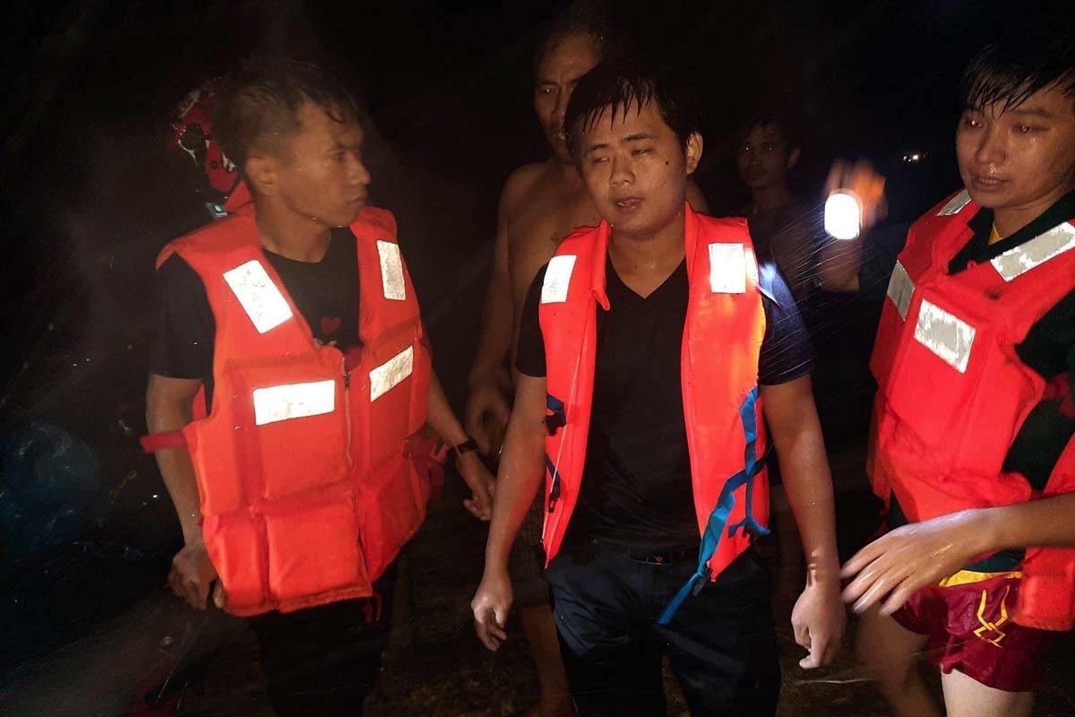 Hùng (giữa) - một trong hai thanh niên được lực lượng cứu hộ đưa lên bờ an toàn, tối 11/9. Ảnh: Sơn Tịnh