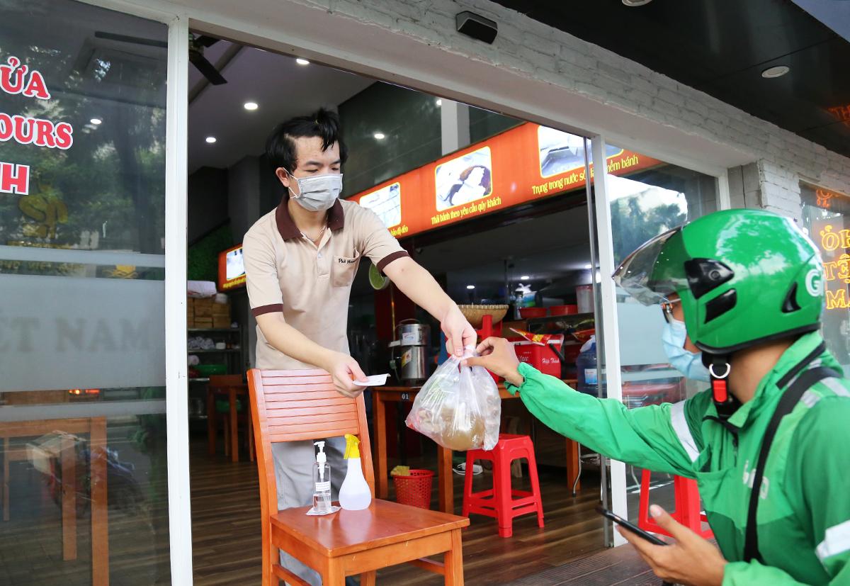 Nhân viên quán phở trên đường Bùi Bằng Đoàn, quận 7 giao hàng cho shipper trong ngày đầu tiên TP HCM cho phép quán ăn bán hàng mang đi, ngày 9/9. Ảnh: Đình Văn