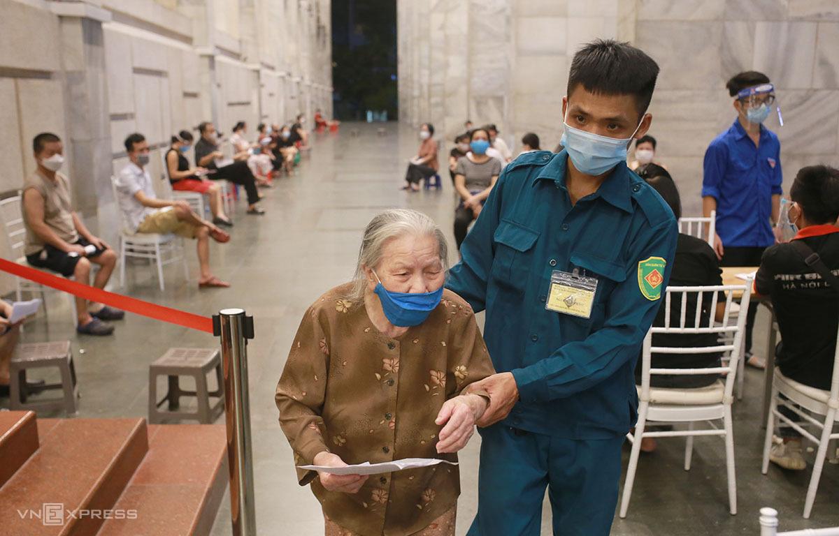 Bà Nguyễn Thị Thoa, 85 tuổi, phường Cửa Đông, quận Hoàn Kiếm đi tiêm vaccine phòng Covid-19 tại điểm tiêm Cung văn hoá hữu nghị Việt - Xô tối 11/9. Ảnh: Tất Định.