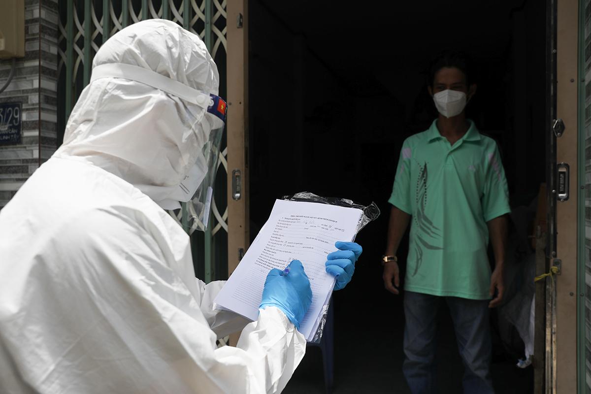 Nhân viên y tế phường Linh Tây, TP Thủ Đức, thăm khám và phát thuốc cho F0 điều trị tại nhà, ngày 3/9. Ảnh: Quỳnh Trần.