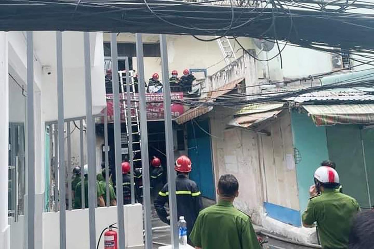 Cảnh sát đeo mặt nạ chống độc, bắc thang cứu người mắc kẹt trong khu nhà trọ cháy. Ảnh: Phòng PCCC TP HCM