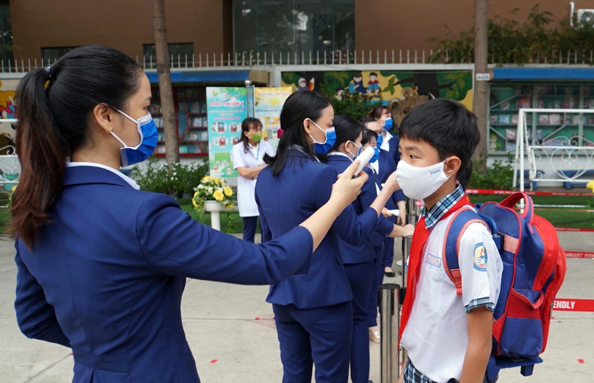 Giáo viên trường Tiểu học Lê Đức Thọ (quận Gò Vấp) đo thân nhiệt cho học sinh trước giờ vào lớp tháng 5/2020. Ảnh: Mạnh Tùng