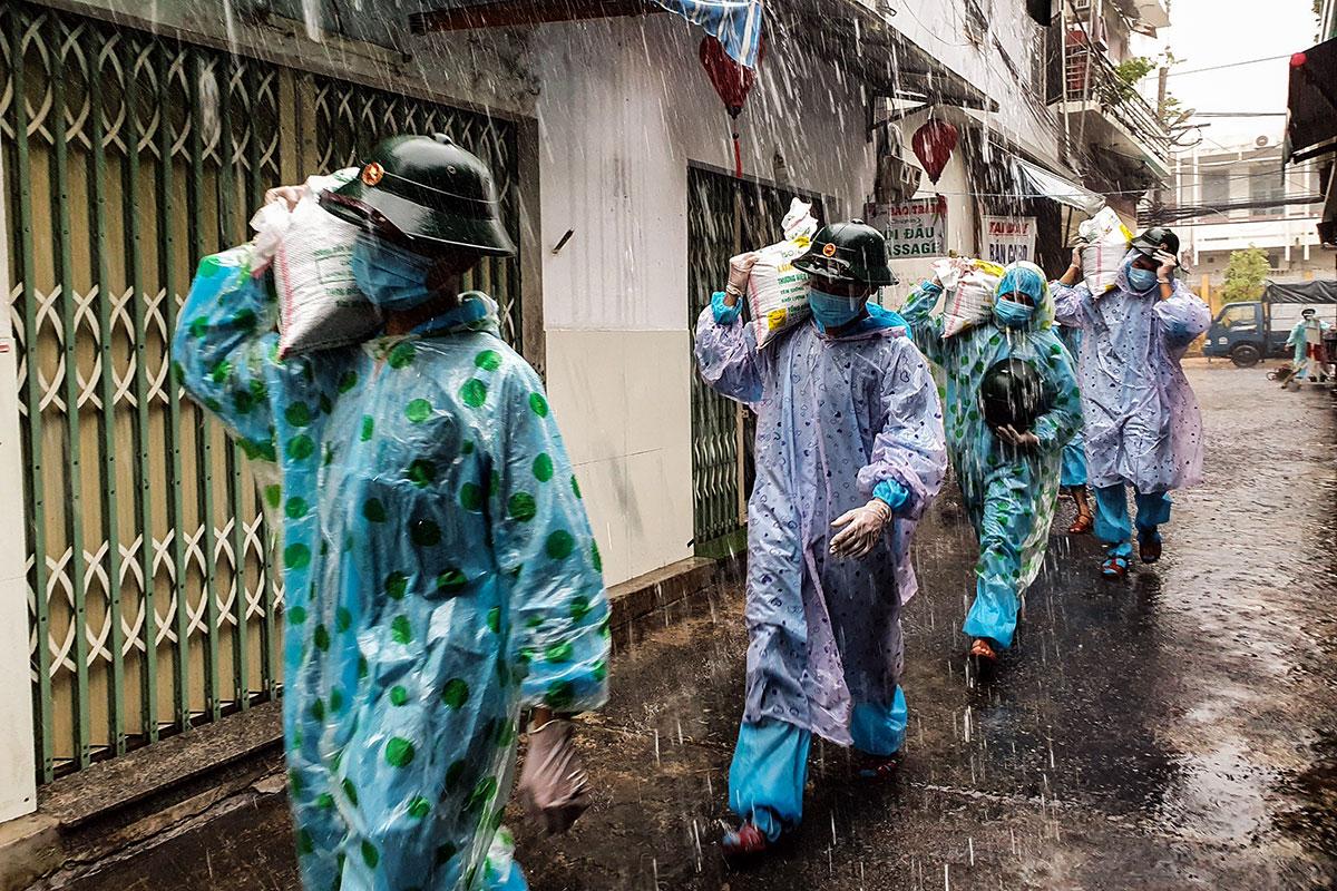 Bộ đội mang đồ bảo hộ và áo mưa vác bao cát gia cố nhà giúp người dân vùng đỏ, sáng 11/9. Ảnh: Giáp Bình