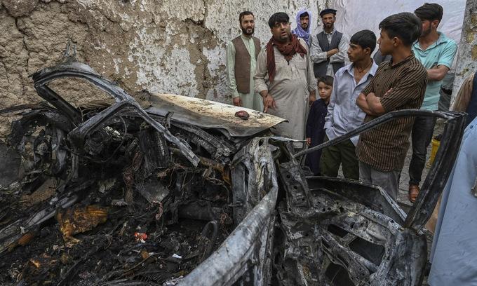 Người thân gia đình Ahmadi bên cạnh chiếc xe bị phá hủy trong đòn không kích hôm 29/8. Ảnh: AFP.