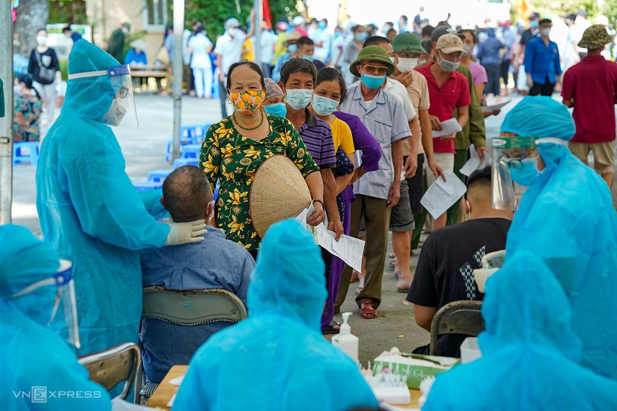Người dân xếp hàng chờ xét nghiệm và tiêm vaccine tại trường tiểu học Đặng Xã, huyện Gia Lâm chiều 9/9. Ảnh: Phạm Chiểu.