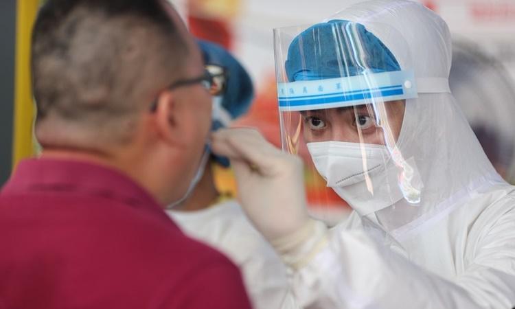 Nhân viên y tế lấy mẫu xét nghiệm Covid-19 cho một người dân ở thành phố Hạ Môn, tỉnh Phúc Kiến, ngày 2/8. Ảnh: Xinhua.