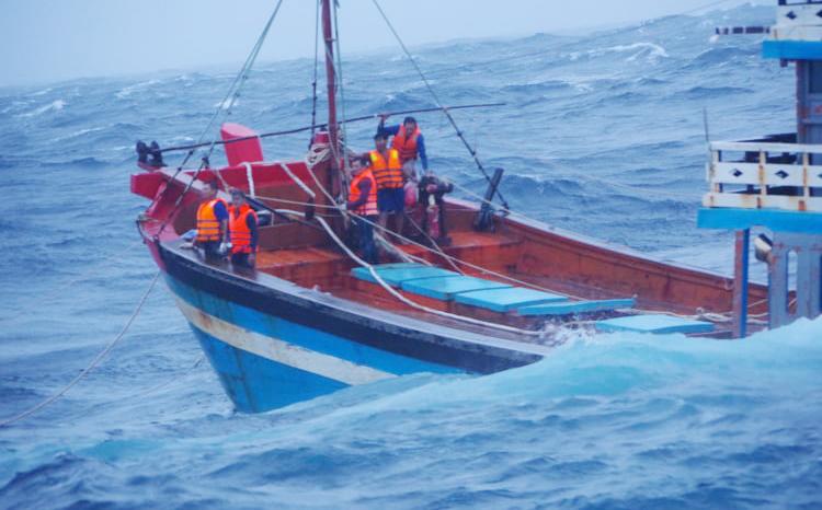 Năm ngư dân tàu Quảng Ngãi đứng ở mũi tàu khi bị chìm phía sau. Ảnh: Cảnh sát biển cung cấp.
