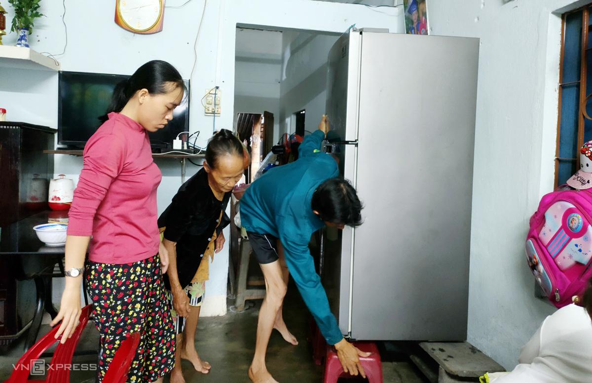 Người dân khu dân cư Mỹ Thạch Trung, phường Hòa Thuận đang kê tài sản lên cao khi nước sắp vào nhà sáng 12/9. Ảnh: Đắc Thành.