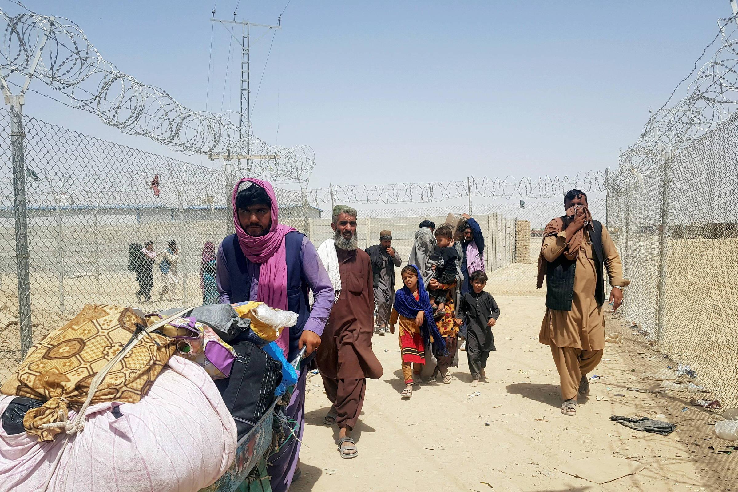 Một gia đình Afghanistan di chuyển tới hàng rào biên giới với Pakistan hôm 6/9. Ảnh: Reuters.