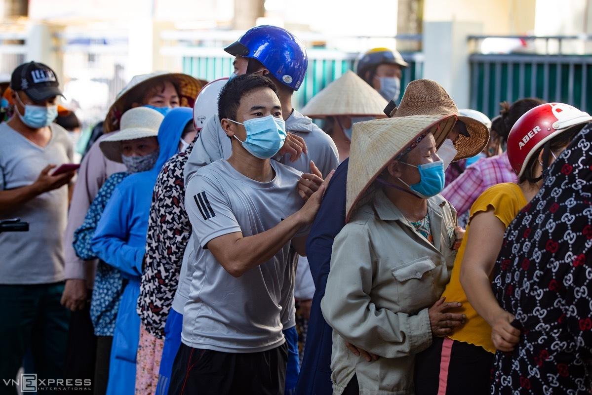 Người lao động chen chân chờ nhận nhu yếu phẩm từ thiện tại đường Mỹ Đình, sáng 7/8. Ảnh: Tùng Đinh