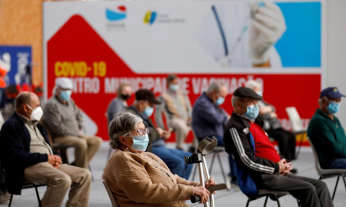 Người dân ngồi chờ tiêm chủng vaccine Covid-19 tại Seixal, Bồ Đào Nha hôm 22/3. Ảnh: Reuters.