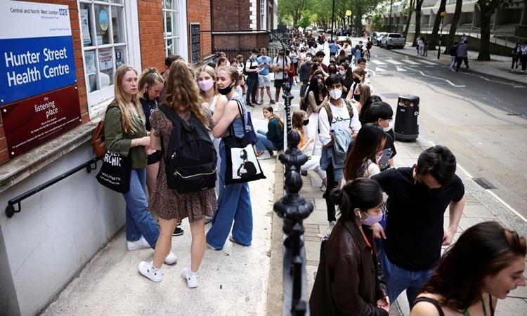 Người dân xếp hàng bên ngoài một trung tâm tiêm chủng ở London, Anh, hồi tháng 6. Ảnh: Reuters.