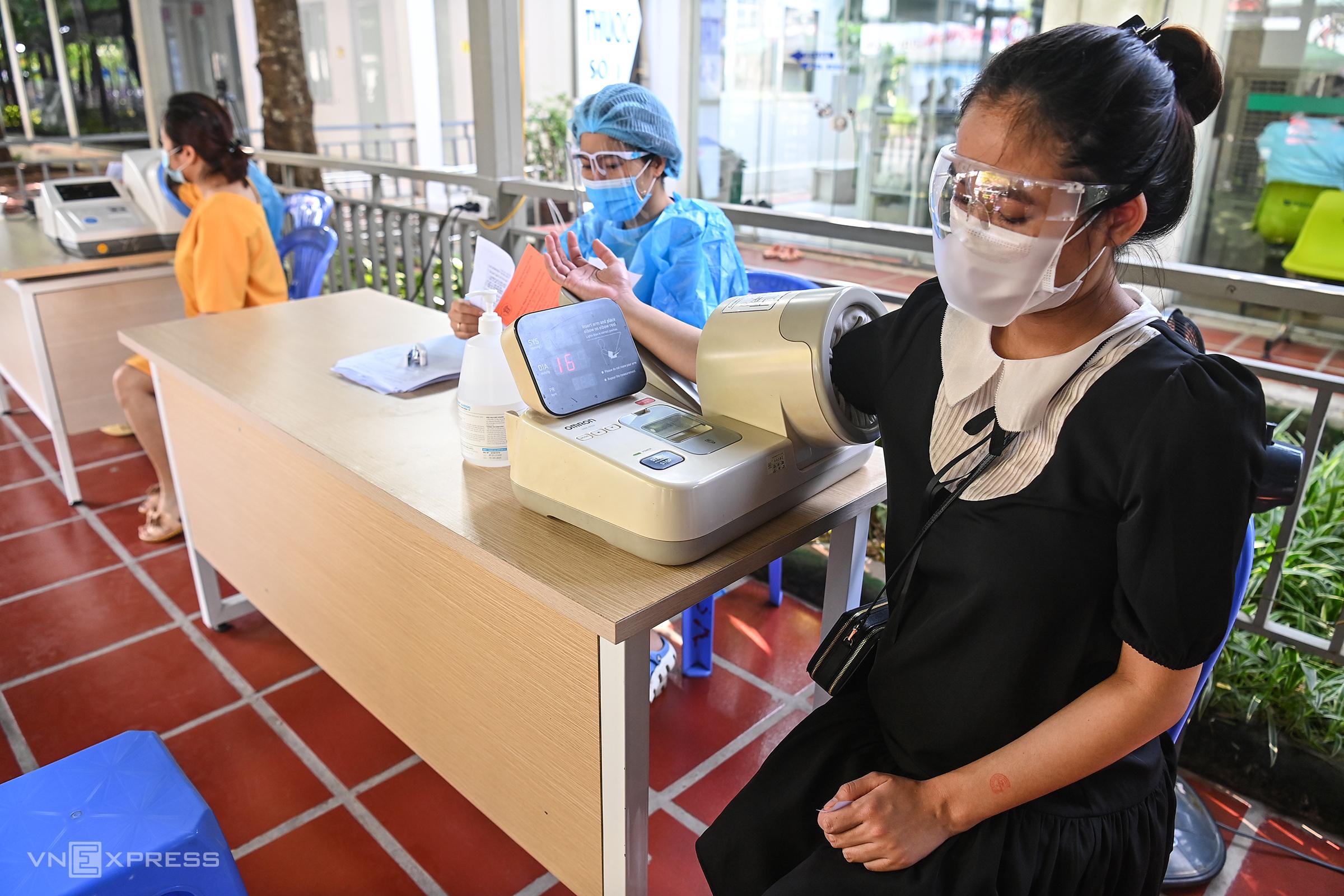 Sáng 11/9, một người dân được đo huyết áp, kiểm tra sức khỏe trước khi vào khu vực tiêm tại Bệnh viện Thanh Nhàn, quận Hoàng Mai. Ảnh: Giang Huy