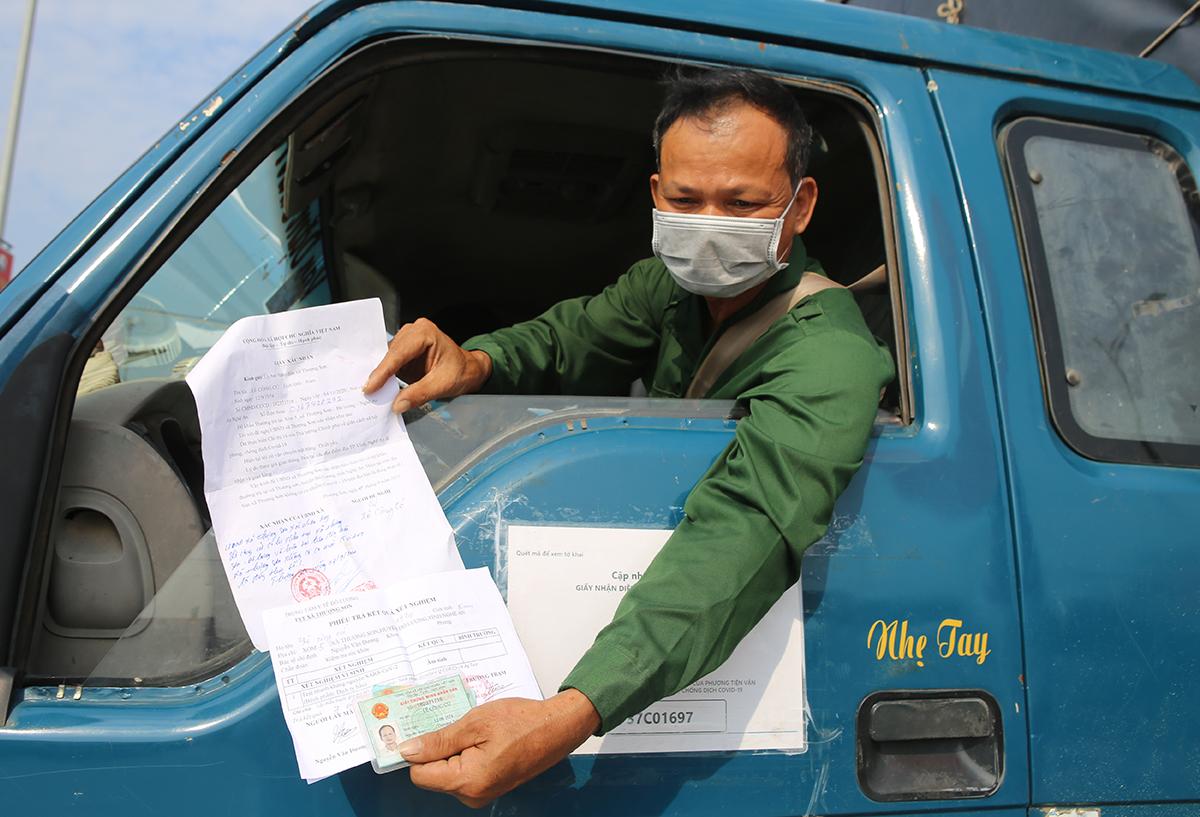 Tài xế chuẩn bị các giấy tờ trước khi tới chốt. Ảnh: Nguyễn Hải