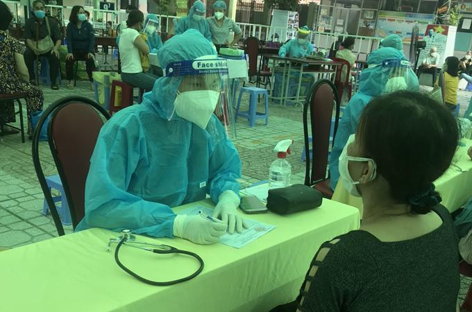 Chị cả Tú Linh đang thăm khám ban đầu cho người dân trước khi tiêm. Ảnh: Nhân vật cung cấp