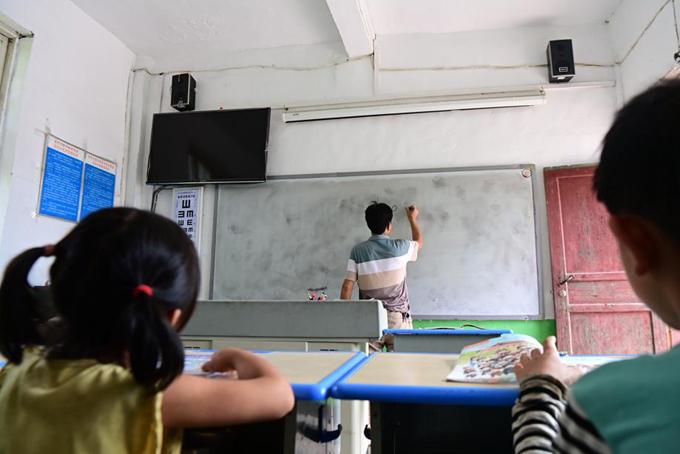 Năm nay, thầy Li chỉ có hai học sinh và đảm nhiệm các môn từ tiếng Trung, toán, khoa học, giáo dục thể chất đến nghệ thuật. Ảnh: China Daily